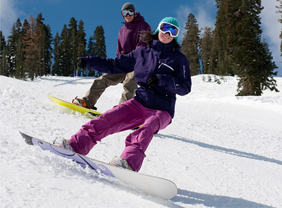 Ski Rental Rates - Snowboarders riding groomers