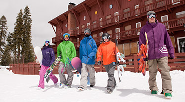 The Lodge at Sugarbow - Snowboarders walking to the lifts with the lodge int he backgroundl